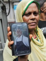 Johura Begum shows a photograph of her brother-in-law Saidul Islam, who works at the Holey Artisan Bakery and is currently missing.