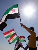 Syrian Kurds living in Lebanon hold the pre-Baathist flag of the Syrian rebellion alongside Kurdish nationalist flags.