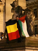 A man waves a Belgian and a Palestinian flag as a mark of solidarity at the Place de la Bourse on Tuesday.