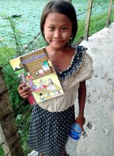 "A girl from the island of Seikkyi, one of Myanmar's poorest neighbourhoods holds the book ""Where women have no doctor"". Photo: Daisy Dumas."