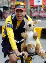 After winning the Tour de France in 2011, Cadel Evans cycles down the Champs-Elysees during the victory parade in Paris.