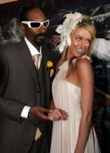 "Suited rapper Snoop Dogg with model Jennifer Hawkins. ""The party vibe went up 100 per cent"" when he arrived at a Birdcage marquee, recalls an organiser."