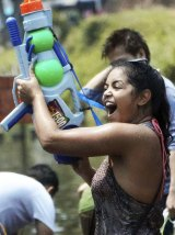 A foreign tourist holds a water gun as she takes part in a water fight during traditional Thai New Year celebrations or Songkran festival in Chiang Mai