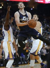 Utah Jazz's Gordon Hayward goes up for a shot between Golden State Warriors' Draymond Green (left) and Andrew Bogut during the second half of the NBA game on Wednesday.
