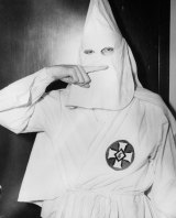 Stetson Kennedy, author of the Ku Klux Klan (KKK) study 'Southern Exposure', posing in the Klan's uniform to illustrate the sign indicating the Oath Of Secrecy in 1947.