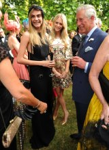 Meeting Prince Charles at a 2013 charity reception with sister Poppy.