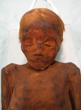 A mummified blonde boy,  about five years of age.