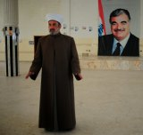 Mufti of Baalbek and Hermel, Khaled al-Solh, in front of a poster of former Lebanese prime minister Rafiq Hariri, who was assassinated in 2005.