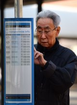 A man checks the timetable for a bus at Strathfield train station during last week's bus strike