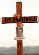 """A cross bearing the name and likeness of Dylan Klebold and a message """"How can anyone forgive you?"""" on a hill in Littleton, Colorado in 1999."""
