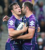 Storm captain Cameron Smith congratulates Cooper Cronk after he scored a try in the round 26 match against Brisbane.