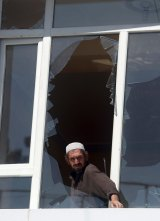 A man removes broken glass from a window after Monday's suicide attack in Kabul.