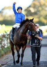 Jockey James McDonald salutes the crowd at Rosehill Gardens after another win.