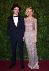 Barely there: Sienna Miller (with partner Tom Sturridge) gives a lesson in showing off a shoulder.