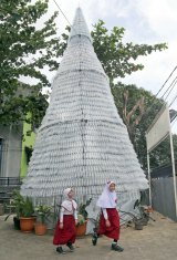 Two school girls walk past a Christmas tree made from 6000 discarded water bottles outside of a church in Depok, Indonesia, this week.