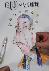 Artist and writer Brian John Spencer works on a cartoon featuring Nigel Farage at the Belfast count.