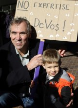 Senator Jeff Merkley, a Democrat, poses with boy and his sign for a family member during a rally in Portland, Oregon.