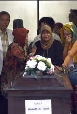 Relatives of Hayati Lutfiah Hamid cry upon receiving her remains at the police hospital in Surabaya.