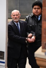 Ian Macdonald is led to the prison truck after being sentenced to a maximum of 10 years in jail.