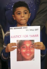 A boy holds a sign demanding action after 12-year-old Tamir Rice was fatally shot by police in Cleveland, Ohio, in November 2014.