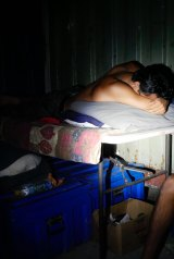 A man sleeping on a fold-out table at the decommissioned Manus Island detention centre.
