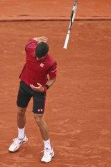 Djokovic throws his racket, narrowly missing a linesman.