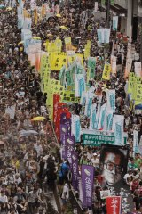 Thousands of protesters march with a picture of Liu Xiaobo along a street during the annual pro-democracy protest in Hong Kong in July.