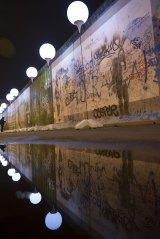 """Balloons of the art project """"Lichtgrenze"""" next to remains of the Berlin Wall."""