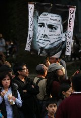 "Demonstrators in Mexico City hold a picture of President Enrique Pena Nieto bearing the slogan ""we want them alive""."
