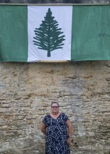 Kim Edward under a Norfolk Island flag at the site of the axed Norfolk Island Legislative Assembly.