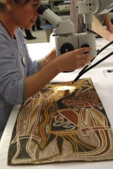 Conservator Chloe Bussenschutt works on a bark painting by David Malangi, Totemic Animals.