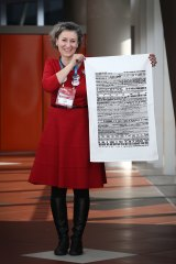 """Lisa Carey, Emily's List national co-ordinator, holding one of the tea towels, says the group wants everyone to remember the speech """"whatever they're doing""""."""