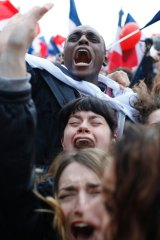 Supporters of French independent centrist presidential candidate, Emmanuel Macron react outside the Louvre museum in Paris.