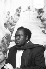 Moses Havini speaking at the opening of an exhibition of artwork by his wife, Marilyn, in 2004. Behind Moses is a painting of members of the Autonomous Government of Bougainville.