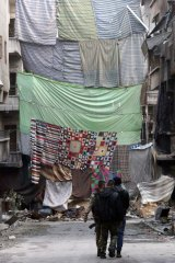 Rebel fighters in the Syrian city of Aleppo walk down a street protected by curtains to obstruct the view of snipers.
