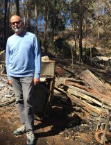 Andrew Holden in front of the destroyed home.