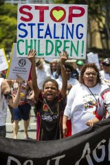 Marchers protest the removal of indigenous children from their families.