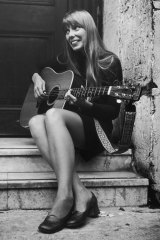 A young Joni Mitchell strums her guitar.