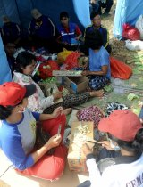 People prepare food at Klungkung sport centre.