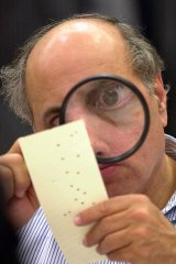 Judge Robert Rosenberg uses a magnifying glass to examine a disputed ballot paper during the Florida recount of 2000.