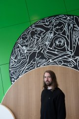 David Booth (Ghostpatrol) in front of one of his  murals at Pauline Gandel Children's Gallery.