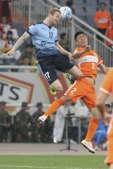 Flying high: David Carney and Zhao Mingjian of Shandong Luneng compete for the ball on Wednesday night.