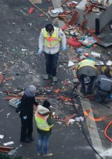 Forensic experts sift through debris in their hunt for evidence a day after a truck ploughed into a crowded Christmas market.