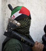 A masked Palestinian youth carries an axe at the funeral of 13-year-old Palestinian Ahmad Sharaka in the Jalazoun refugee camp, near the occupied West Bank city of Ramallah.