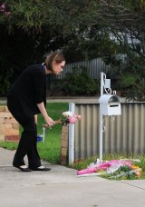 A woman leaves flowers outside the home where a man killed his wife and himself with a high-powered rifle.