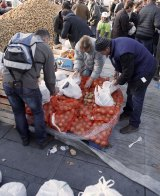 Country comes to town: Farmers from the French farmers unions distribute potatoes and fruits to residents after dumping 50 tons of fruit and vegetables during a protest in Place de La Republique.