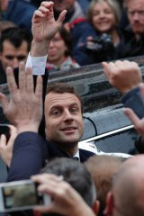 Emmanuel Macron greets well-wishers as he leaves the polling station.
