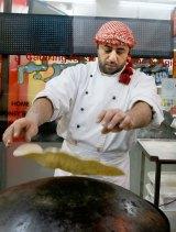 Malek Nasser prepares a Malek a Saj - a type of soft stuffed pita roll.