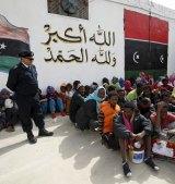 Illegal migrants sit at Abu Saleem detention centre.