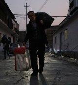 Yan Erjun moves his belongings.